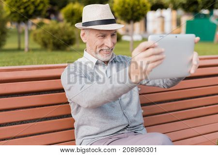 A pensioner sits on a bench in a beautiful square. He has a gray tablet in his hands. He communicates with someone on video communication