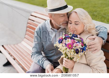 Two pensioners are sitting on a bench in the square. They embrace. A woman has a bouquet of flowers in her hands. They smile happily.