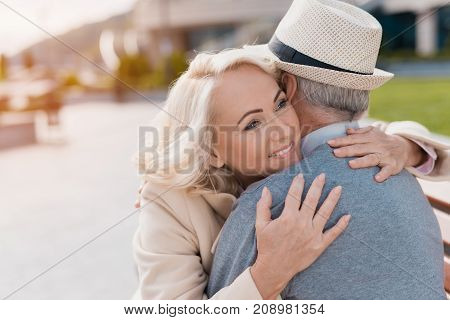 Two pensioners are sitting on a bench in the square. They tenderly embrace sitting on the bench and smile happily