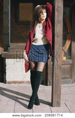 young beautiful stylish woman in claret coat street style spring summer trend dark skirt beige sweater flirty.