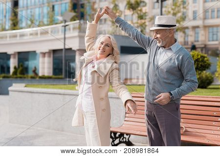 Two pensioners dance on the square near the bench. They are happy and smiling. They perform waltz movements