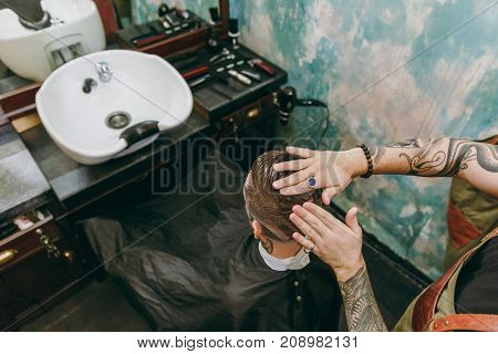Close Up Shot Of Man Getting Trendy Haircut At Barber Shop. Male Hairstylist In Tattoos Serving Clie