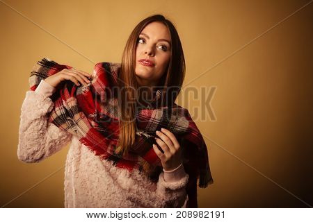 Autumnal outfit concept. Young long haired woman wearing warm autumn clothing woolen checked scarf on beige studio shot