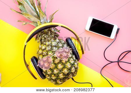Stylish pineapple in sunglasses listen to music on the smartphone on yellow and pink background top view.
