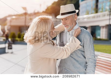 An elderly couple met on the street. A woman is straightening a man's collar. He stands next to her in a white hat. They smile at each other