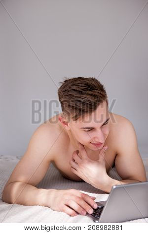 Muscled man with smile have online chatting with girl on bed. Sunny romantic morning at home.