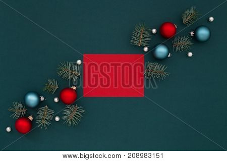 Shaded spruce background with Red greeting card and Christmas decorations balls pearls. Holidays New Year congratulation.