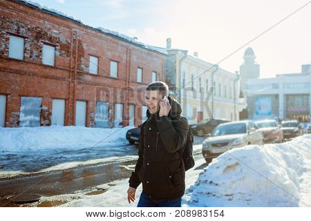 Young man with a backpack goes on the winter city and speaks by phone. Winter hiking tourism and fashion concept.