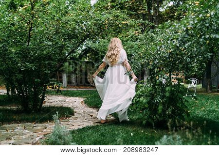 Gorgeous blonde bride in white dress is walking in a green garden among the trees. Back view. Artwork.