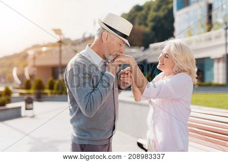 An elderly couple walks in the square. The man gently kisses the woman's hand. She smiles. They are happy