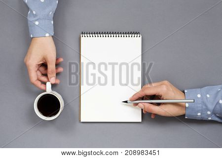 Woman's hands writing in notebook holding cup of coffee on gray workplace. Multitasking concept work and coffee break. Minimal creative playful. Top view.
