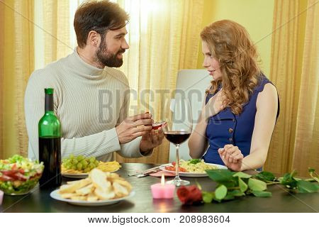 Man giving ring to woman. Couple having a romantic dinner. Engagement surprise ideas.