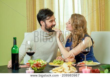 Woman feeding man. Couple having dinner. Tasty food and romantic atmosphere.
