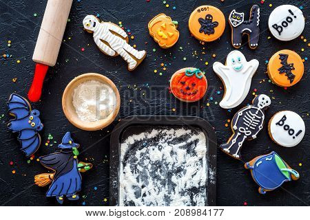 Cook halloween gingerbread cookies bat, skeleton, ghost. Sweets near rolling pin and baking sheet. black background top view.