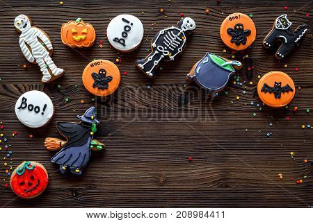 Cook halloween gingerbread cookies with witch, skeleton, ghost. Wooden background top view.