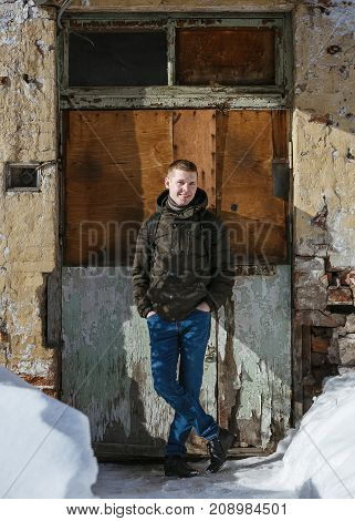 Young man posing with a trendy outfit against a vintage urban background.