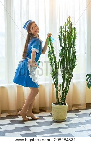 Young housemaid smiling. Attractive woman at work. Psychology of flirting.