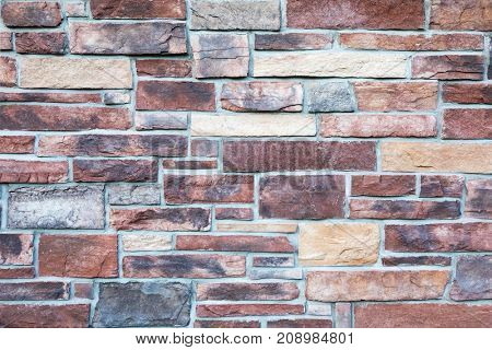 Block stone wall background in warm tones.