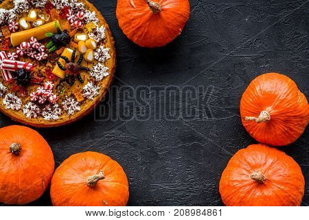 Homemade pie for halloween decorated gummy spiders among pumpkins on black background top view.