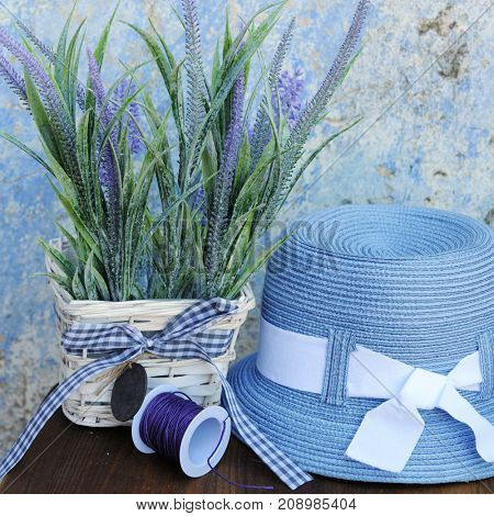 Sun hat and lavender flowers against old cracked wall in Greece, touristic concept
