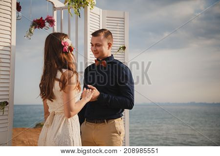 Outdoor beach wedding ceremony, stylish happy smiling groom and bride are standing near wedding altar on the sea shore holding hands together.