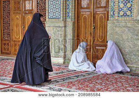 Fars Province Shiraz Iran - 19 april 2017: Parishioners sit in courtyard of Shah Cheragh Shrine mosque.