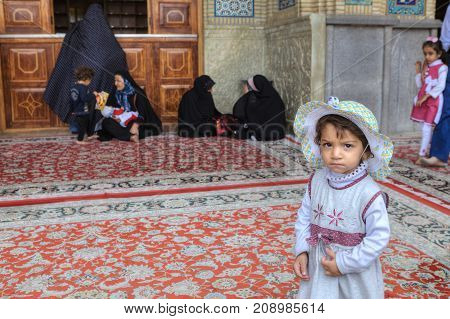 Fars Province Shiraz Iran - 19 april 2017: Shah Cheragh Shrine Portrait of an unknown little girl about four years old standing in the courtyard of the mosque on the background of pilgrims.