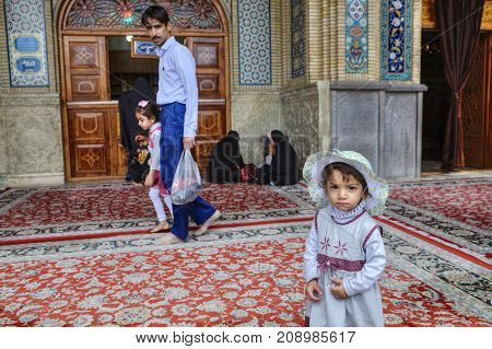 Shiraz Iran - 19 april 2017: Shah Cheragh ShrineOne unknown Iranian girl in the beach hat about 4 years old stands in the courtyard of the mosque against the background of the parishioners.