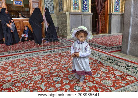 Shiraz Iran - 19 april 2017: Shah Cheragh Shrine An unknown little girl about 4 years old wearing a beach headdress stands at entrance to mosque near a group of women in black Muslim clothes.