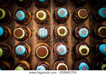 A wide top down shot of colorful icing covered covered cupcakes all put in a row.