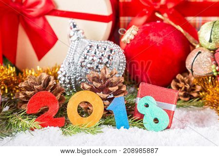 Christmas or New Year card. 2018 colorful figures near cones decorative christmas balls and gift boxes on snow and fir tree branches. Focus on figures