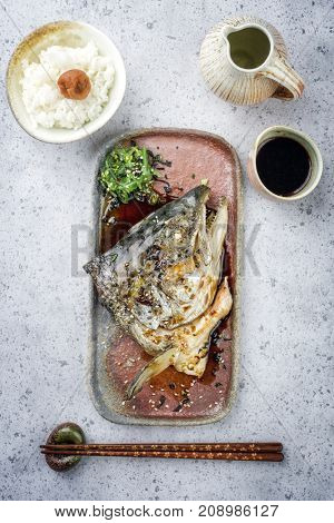 Traditional barbecue Japanese Kama Yaki broiled salmon fish head with rice and umeboshi as close-up on a plate