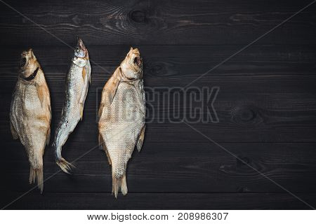 Dried fish breams and smelt candle fish on dark wooden table with copy space