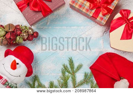 Christmas or New Year card. Funny snowman with gift-boxes fir tree branch Santa head on snowy blue wooden background