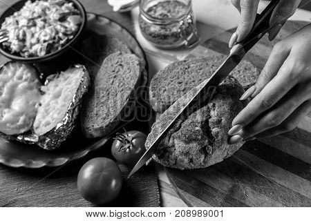 Preparation of potatoes with mushrooms and vegetables with sauce black and white poster