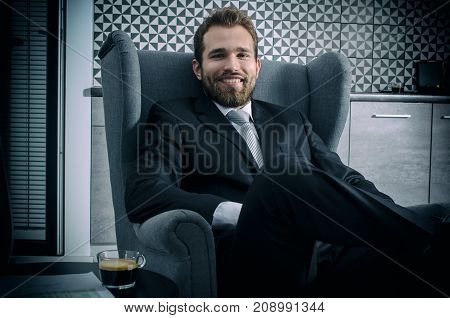 Businessman Sitting On An Armchair In Home