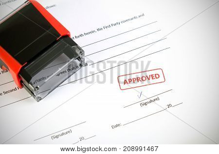Automatic stamp on the contract document. Approved agreement. approve permit paperwork document automatic stamp authority agreement concept