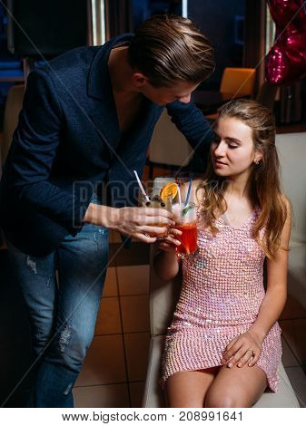 Seductive talks at Christmas party. Flirty stylish male, romantic atmosphere with drinks, night club background. Modern youth celebration, seduction concept