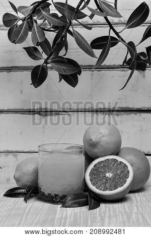 orange lying on a wooden table with leaves black and white poster