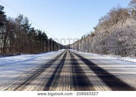wide asphalt road in the winter season. Ruts from cars on the roadway