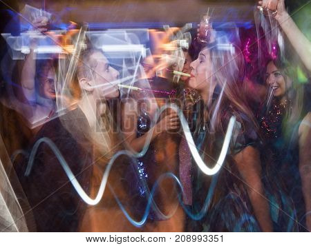 Joyful New Year couple dancing in motion. Active Christmas celebration in night club. Disco party in blurred colors, modern youth life