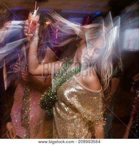 Active dancing female in night club in blurred motion. Friends at Christmas discotheque, New Year company with drinks, modern youth life