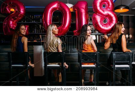 New Year party at bar. Beauty females. Stylish women group, friends celebration. Club background, festive mood