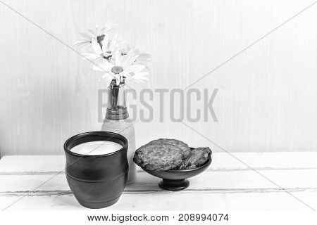 Daisies and cookies and milk on the table black and white