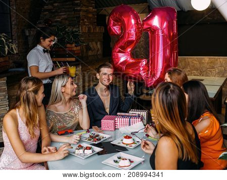 Happy 21 birthday party celebration with friends. Joyful mood, youth company in cafe with balloons. Modern leisure time, festivity concept