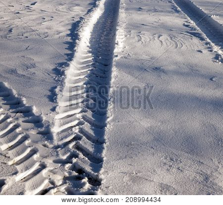 traces of a truck on white snow. close-up photo