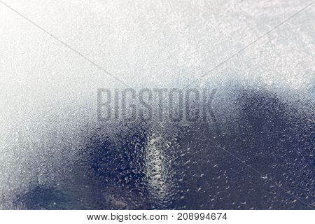 photo of a frost on the dirty glass of the car. close up