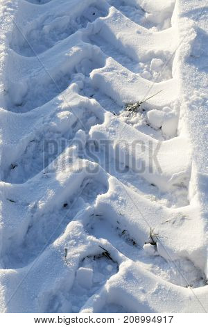 snow drift by which they drove a heavy tractor and made traces on the surface. close-up photo