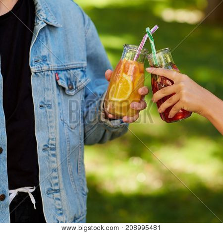 Healthy nutrition. Friends drinking fresh juice detox on green nature background. Youth lifestyle, vegetarian diet to go, fitness food, successful weight loss concept