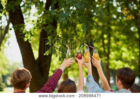 Group of people celebrate with detox juice cocktails on green nature background witn free space. Diet on the go, well being and weight loss, superfoods, health, vegetarian food concept